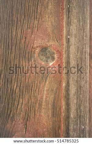 Looking at a crack in the wood plank barn wall with a big knot
