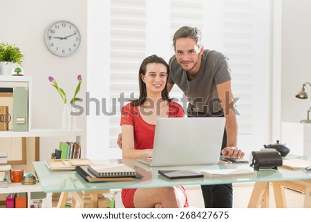 Looking at camera, at office, business-team examining a project together on a laptop, the office is modern and bright - stock photo
