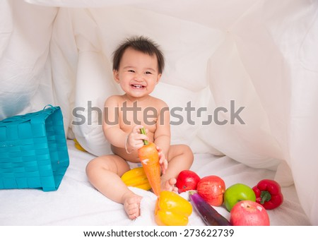 looking at fruit cute smiling baby on white background among fruits. Photo with depth of field - stock photo