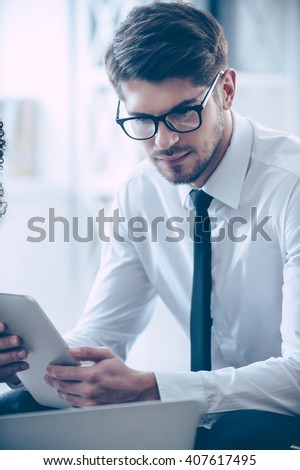 Looking at his timetable.  Close-up part of young handsome man in glasses using his digital tablet while sitting at the office table  - stock photo
