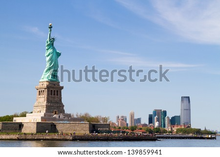 Looking at Statue of Liberty from the floating boat, with Manhattan Skyline far behind - stock photo