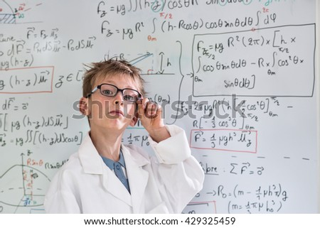 Looking at the camera, funny little boy posing as a scholar in front of a white board with mathematical formulas, he wears a white coat and glasses