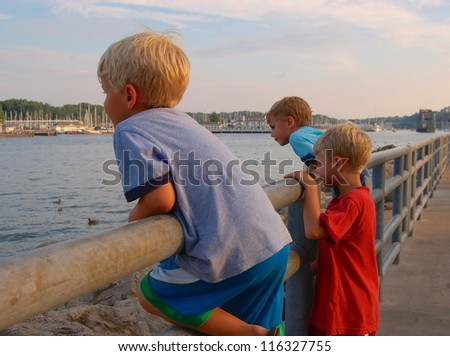 Looking at the River/Boys rest against the fence and 	look at the river - stock photo
