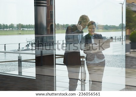 Looking at two business people next to office in city through glass - stock photo