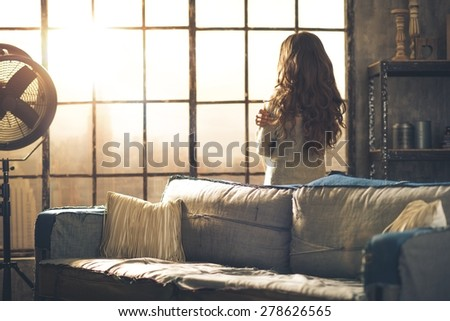 Looking away, a brunette woman in comfortable clothing is standing in a loft living room, hugging herself, looking out the window. Urban chic loft decoration details and window. - stock photo