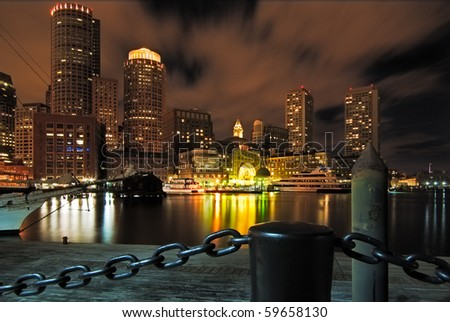 Looking back towards Boston fromRowe's Wharf at night with the city lighting up the sky - stock photo