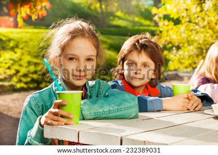 Looking boy and girl with green cups sit at table - stock photo