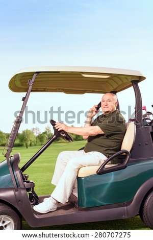 Looking busy. Portrait of senior man sidewise using mobile phone and driving cart on course. - stock photo