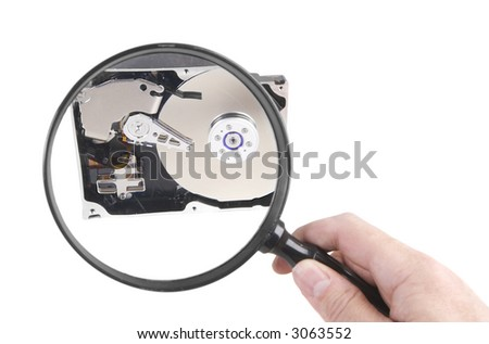 Looking closely at a hard drive with a Magnifying glass (concept) - stock photo