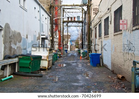 Looking down a long dark back alley. - stock photo