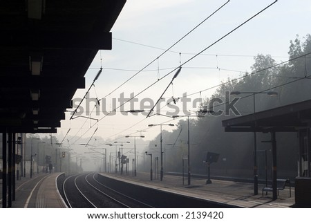 looking down a railway train station on a misty morning - stock photo