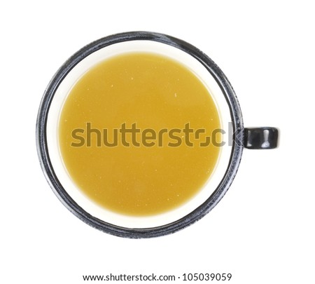 Looking down at a bowl of canned chicken broth. - stock photo