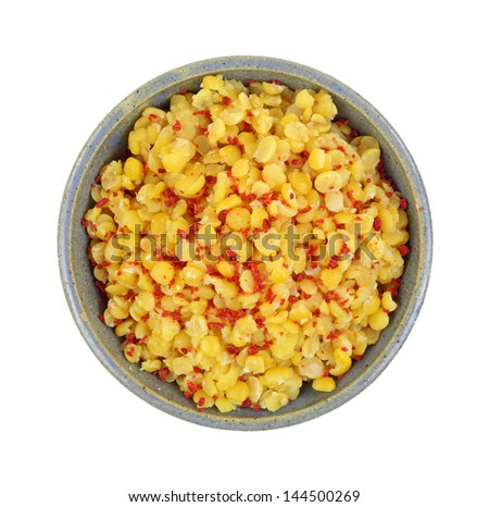 Looking down at a bowl of cooked yellow split peas with bacon bits. - stock photo