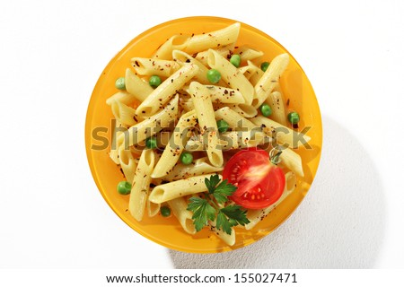 Looking down at a plate of cooked tubular pasta with seasoning herbs / top view of flavored macaroni noodles served with green parsley and tomato in an orange plate  - stock photo