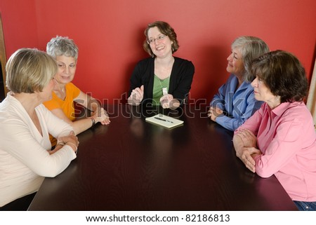 Looking down at four senior woman sitting around a table with a younger woman leading a discussion. - stock photo
