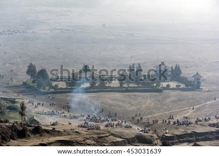 Looking down at the misty morning of caldera sea-sand plain from Mount Bromo. Tourist can be seen flocking around taking selfies, walking and horseback riding along the route to volcano crater.
