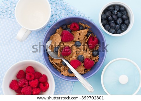 Looking down from above onto a healthy breakfast table with cereal, raspberries and blueberries in bowls.