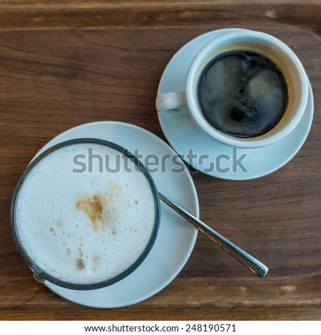 Looking down on a cafe latte and black coffee sitting on a tray. - stock photo