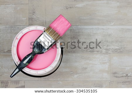 Looking down on a can of Pink Paint with a loaded brush stood on a shabby style wood floor - stock photo