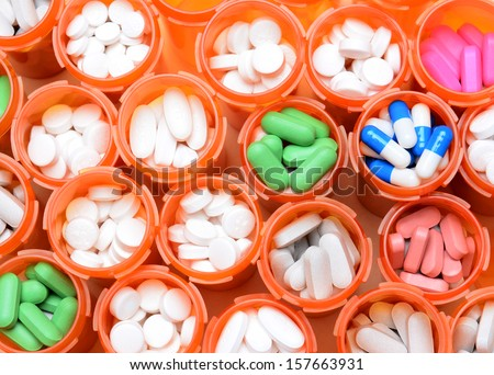 Looking down on a large group of prescription medicine bottles. The bottles all have their caps off and have a variety of drugs, tablets and capsules. Horizontal format filling the frame. - stock photo