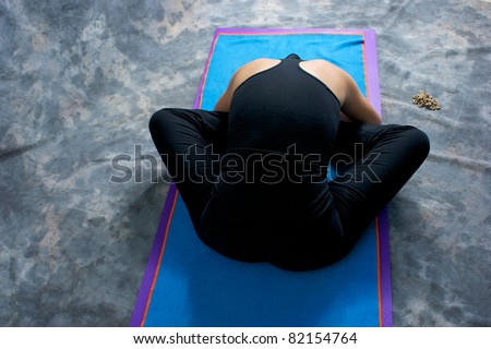 Looking down on an athletic brown haired woman from behind doing yoga exercise Bound Angle Forward Bend pose on yoga mat in studio with mottled background. - stock photo