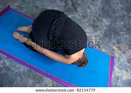 Looking down on an athletic brown haired woman is doing yoga exercise rabbit pose on yoga mat in studio with mottled background. - stock photo