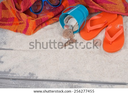 Looking down on Beach Still Life. Towel, Bucket, Seashells, Orange Rubber Sandals, Swim Mask on top, Room or space for copy, text, words rustic board walk sand background. Horizontal  - stock photo