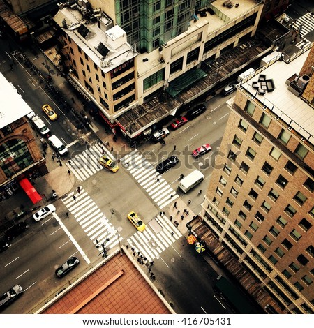 Looking down on to the streets of New York City with New York yellow taxis and people crossing the street going to work. Instagram style image. - stock photo