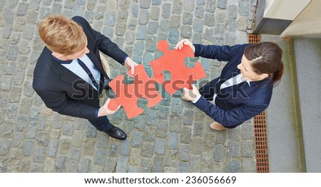 Looking down on two business people solving a big red jigsaw puzzle - stock photo