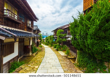 Looking down restored stone footpath on ancient Nakasendo trail densely lined with traditional wooden houses under overcast daytime clouds in Magome, Kiso Valley, Japan
