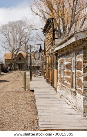 Looking down the dirt street of the ghost town of Nevada City, Montana, past the blacksmith shop to a once lovely home at the end