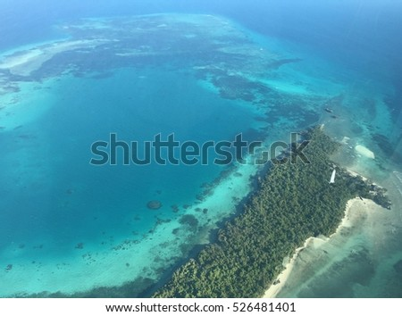 Looking down view of a little green Island in the middle of the Indic blue turquoise ocean surrounded by coral reefs