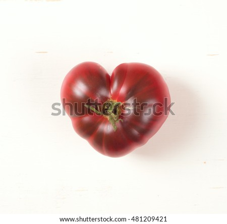 Looking Down View of the Top of One Heart Shaped, Red Tomato on a Rustic White Board Background.  It is centered and a purple variety tomato with dark streaks.