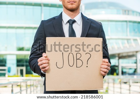 Looking for a job. Close-up of young man in formalwear holding poster with job text message while standing outdoors and against building structure