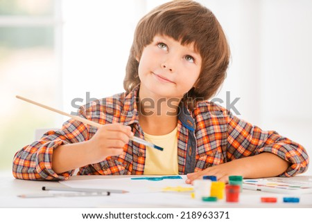 Looking for inspiration. Cute little boy relaxing while painting with watercolors sitting at the table - stock photo