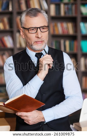 Looking for inspiration. Thoughtful grey hair senior man in formalwear holding note pad and looking away while leaning at the table and with bookshelf in the background - stock photo