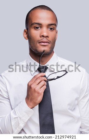 Looking  for inspiration. Thoughtful young African man in shirt and tie holding eyeglasses and looking away while standing against grey background  - stock photo