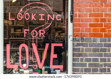 Looking for love written in pink ink on a shop window in Shoreditch (London) - stock photo