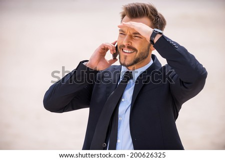 Looking for new solutions. Cheerful young man in formalwear working on laptop while sitting on sand in desert - stock photo