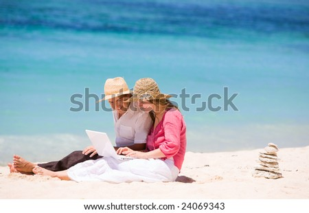 Looking for perfect vacation. Happy couple using laptop on the beach. - stock photo