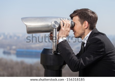 Looking for solutions. Side view of cheerful young men in formalwear looking through stationary binoculars and smiling - stock photo