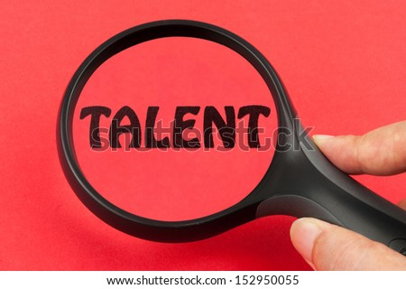 Looking for talent concept with a magnifier on hand - stock photo
