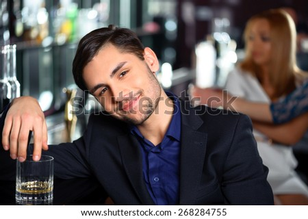 Looking for the new acquaintance. Young handsome man relaxing with a drink in the bar