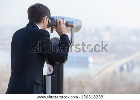 Looking forward. Rear view of young men in formalwear looking through stationary binoculars - stock photo