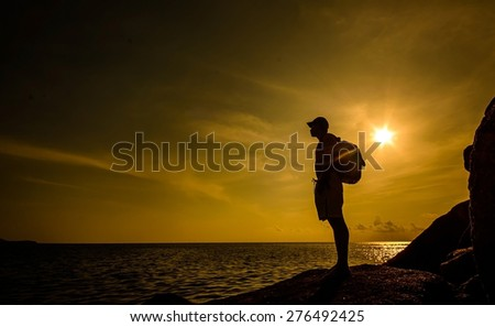 Looking forward with silhouette of a man stand on large rock at the beach on sunset time