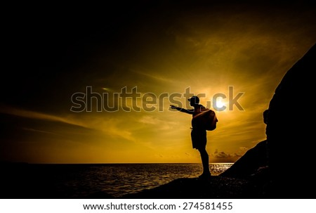 Looking forward with silhouette of a man stand on large rock at the beach on sunset time,Focus on a man and blurry on water