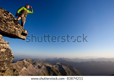 Looking forward. Young man overlooking mountain range - stock photo