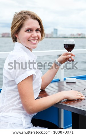 Looking from back woman holding red wine glass and sitting at the cafe table - stock photo