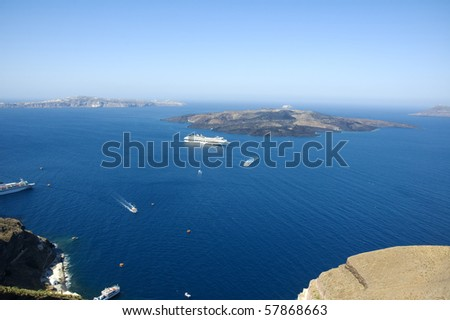 Looking from Santorini island into the Caldera and the Aegean sea in the distance with a cruise ship and ferry boats - stock photo