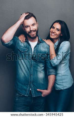 Looking great and feeling happy. Studio shot of beautiful young couple in jeans wear standing close to each other and looking at camera with smile - stock photo